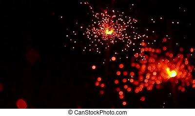 Three red sparklers against dark background. Super slow...