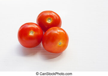 Three red tomatoes on a white .