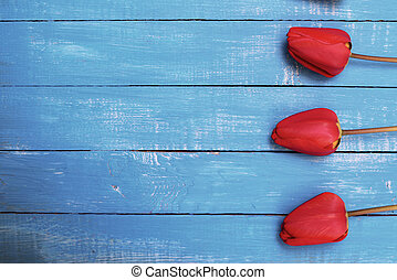 Three red tulips on a blue wooden surface