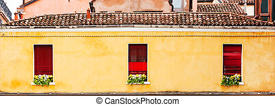 Three red windows with flowers of a typically Italian house.