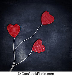 three red wooden hearts on a white string