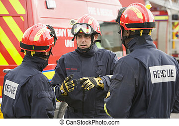 Three rescue workers talking by rescue vehicle