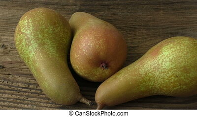 Three ripe juicy pears on a dark wooden table