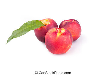 Three ripe peaches with leaves