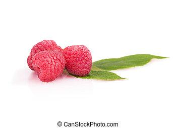 Three ripe raspberries with leaves