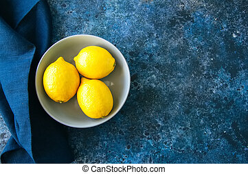 Three ripe yellow lemons in a grey bowl on a blue stone background. Top view and copy space.