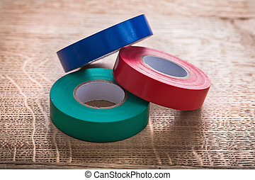 three rolls of insulating tape on wooden board construction ...