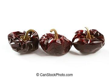 Three round Mediterranean dried dark red peppers