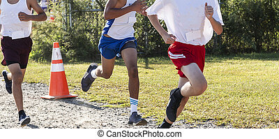 Three runners racing to the finish during a high school cross country race