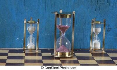 Three sand clocks on chess board with sand running - Three...