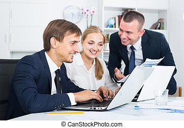 Three satisfied coworkers different sexes working in company office