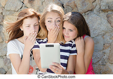 Three scared teen girl friends and tablet computer