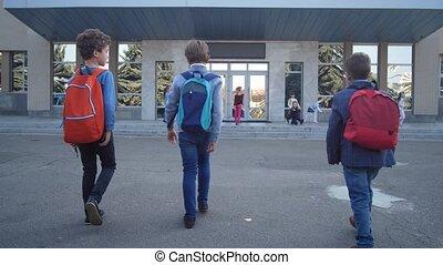 Three schoolboys walking to school doors