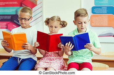 Three schoolchildren reading books at school