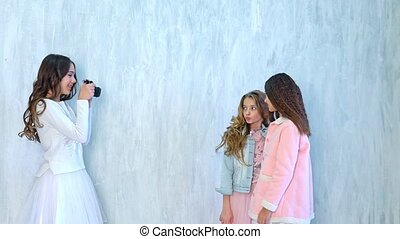 three schoolgirl girls take pictures of each other