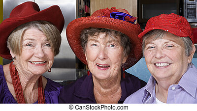 Three Senior Women Wearing Red Hats - Three friendly senior...