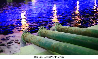 sewage pipes - Three sewage pipes discharging water into the...