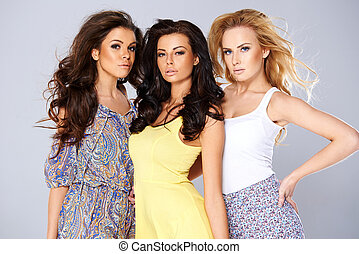 Three sexy chic young women in summer fashion standing arm...