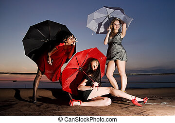 Three sexy chicks with umbrellas posing on the roof