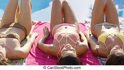 Three sexy girlfriends sunbathing in bikinis
