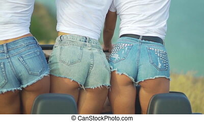 Three sexy girls in denim shorts move their buttocks....
