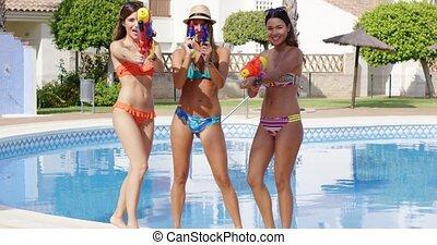Three sexy young woman aiming at the camera - Three sexy...