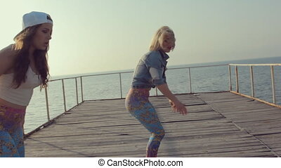 Three sexy young women dancing twerk on a wooden pier near the sea