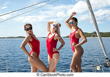 Three sexy young women in red bikinis seductively moving on a yacht in the open sea