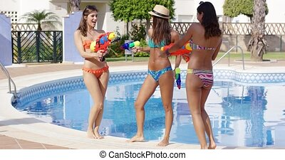 Three sexy young women playing with water guns at the side...