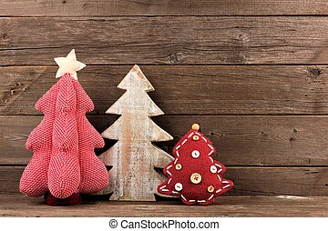 Three shabby chic Christmas trees against wood - Three...
