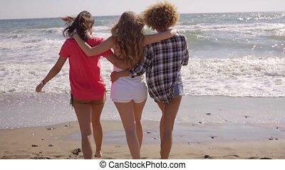 Three shapely female friends walking on a beach