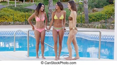 Three shapely sexy women in bikinis poolside