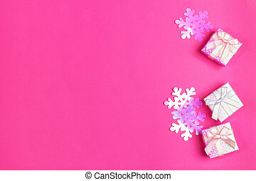 Three shiny gift boxes with bows and iridescent plastic purple snowflakes on bright pink background. Christmas festive presents. Top view, copy space.