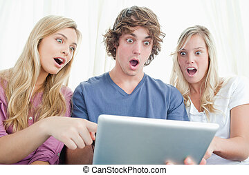 Three shocked friends looking at the screen of the tablet
