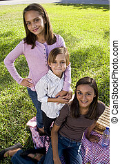 Little boy and two older sisters posing for camera sitting on picnic blanket in park
