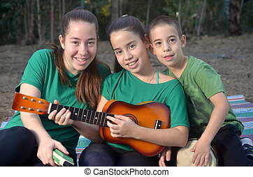 Three siblings (two older sisters and their little brother) in a forest is Israel playing musical instruments