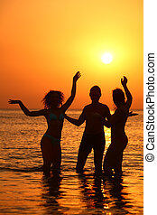 Three silhouettes in sea on sunset
