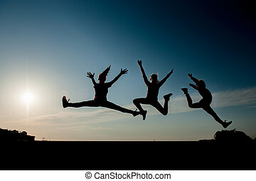 three silhouettes of jumping teen girls on blue sky background at sunset