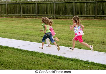 Three sister girls playing running on the park