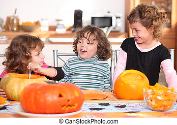 Three sisters carving pumpkins.