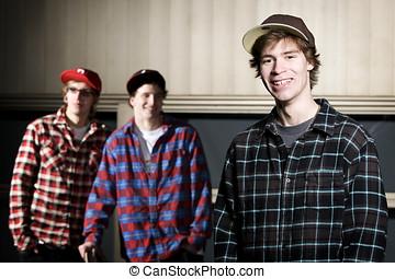 Three skateboarder kids standing together smiling