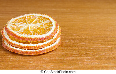 Three slices of dried orange on wooden table