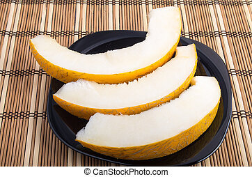 Three slices of juicy yellow melon on a black plate