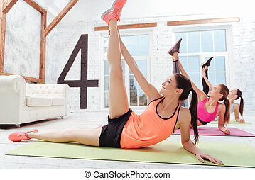 Three slim women doing stretching in gym