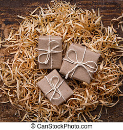 Three small gifts are wrapped in kraft paper and lay in wood shavings. Handmade gift concept, eco-friendly packaging. Top view