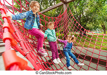 Three small girl sitting on red grid in summer