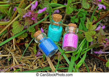 three small glass bottles with red and blue sand among grass plants and lilac flowers