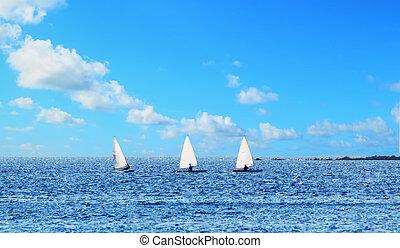 three small sail boats in a row