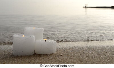 Three small white paraffin candles burning on sandy beach shore edge near gray sea ocean waves burning on shore in day close-up. Concept fire romance relax mood burning calm weather background.