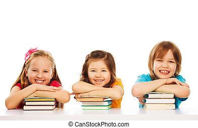 Three smart kids on pile of books